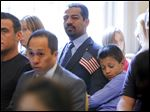 Taleb Al Zakwani, 8, hugs his father,  Mohamed Said Al Zakwani, formerly of Oman, during a naturalization ceremony at the Manor House in Wildwood Preserve Metropark on Monday.