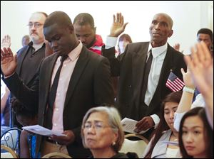 Earl Darlington Edwards, right, Toledo, formerly of Jamaica, takes the Oath of Citizenship.