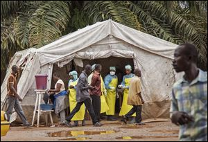 Health workers, center rear, screen people for the deadly Ebola virus before entering the Kenema Government Hospital.