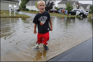 Ethan Rader, 5, of Perrysburg, fills his boots with water from heavy rains in the Brookhaven subdivision in Perrysburg.