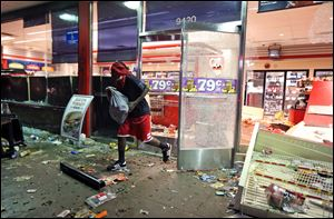 A man leaves a store after a looting Sunday in Ferguson, Mo.