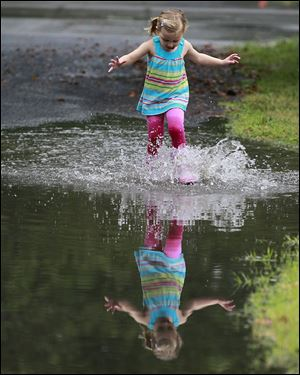 Lucy Baechle, 3, plays in the flooded street of Brookford Drive in Toledo after one of Monday's torrential downpours.