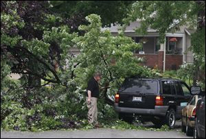 Frank McKinney moves branches from a large downed tree branch that fell across Vasser Street so his wife, Lisa, can pull into the driveway of their Toledo home.  The tree is blocking the entire street.