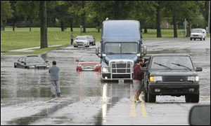 Stranded motorists look over flooded vehicles earlier today in Dearborn, Mich.