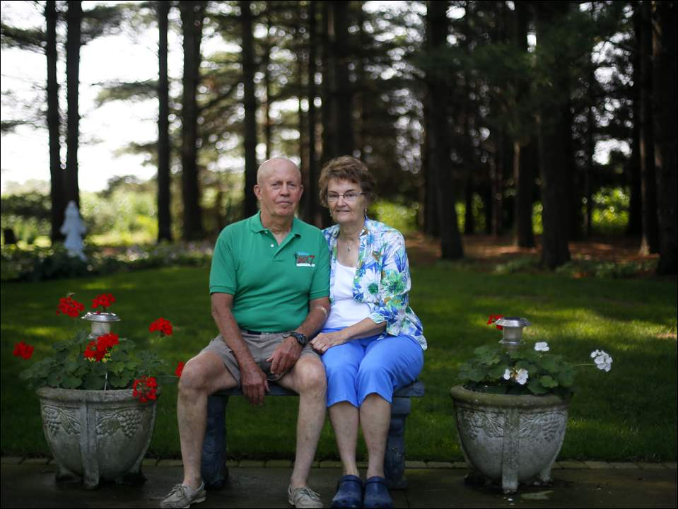 Johanna Mack and her husband Bill Mack sit on a bench in one of their many garden areas on her property.