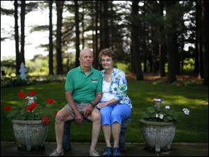 Johanna Mack and her husband Bill Mack sit on a bench in one of their many garden areas on her property