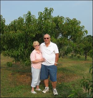 Jennifer and Bill Ely stand in front of a nectarine tree that was standed from a pit.