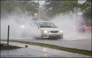 Cars splash their way on Talmage Road on Monday. Serious rainfall ended a run of dry weather, forcing many area roads to close, swamping houses, and prompting tornado worries. In some spots in Perrysburg, 5 to 6 inches of rain had fallen by 2 p.m., according to the National Weather Service.