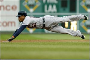 Detroit Tigers' Ezequiel Carrera (61) dives for second base with a double in the first inning.