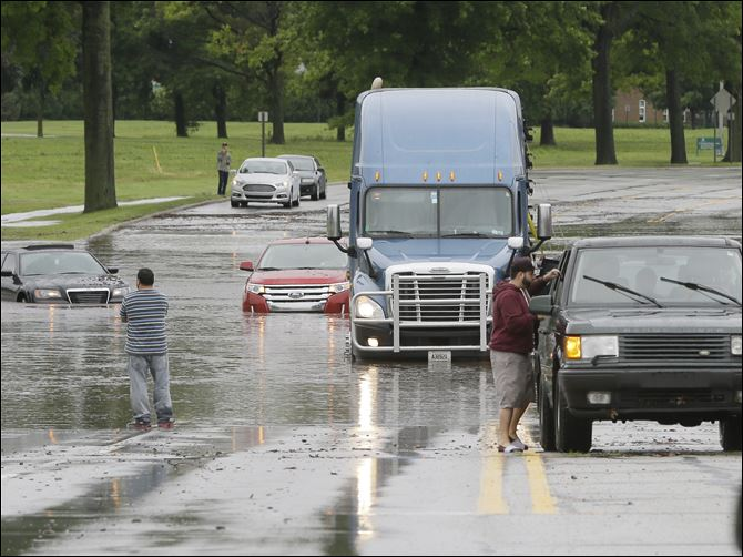 Flooding Michigan Stranded motorists look over flooded vehicles, Monday,   in Dearborn, Mich. The Michigan State Police issued an advisory Monday evening, urging drivers to avoid non-essential use of all metro Detroit freeways after heavy rain and thunderstorms left roads flooded and impassable.
