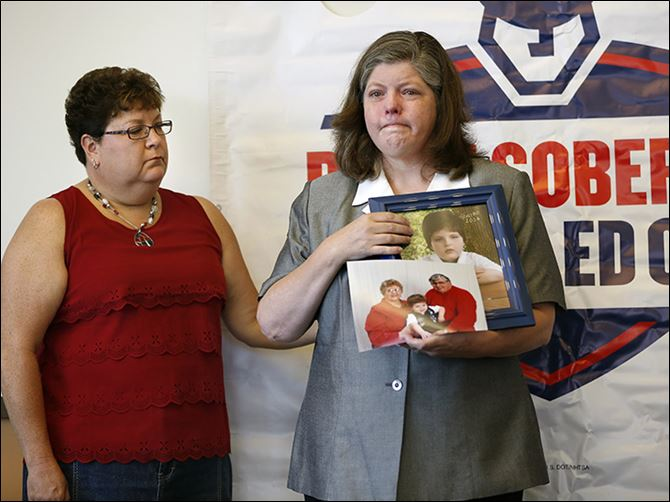 n4driving-1 Shelen Stevens of Weston, Ohio, holds photos of her deceased parents, Bill and Sharon DeWitt, and her son at a news conference on Tuesday at the Ohio Highway Patrol post in Bowling Green. At left is Sandy Wiechman, BGSU safe communities coordinator.