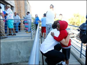 "Capt. Tawny Cowen-Zanders, left, hugs Malachi Winston, 4, right, from Toledo, while greeting people waiting in line to get backpacks with school supplies during The Salvation Army's Annual ""Tools for Schools"" Distribution at The Salvation Army on August 13, 2014. Huntington Bank has donated more than 1,800 backpacks to give to local families in need, with The Anderson's and the community donating additional supplies."
