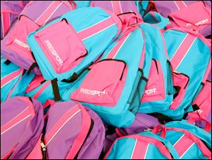 A mountain of girl's backpacks to be distributed.