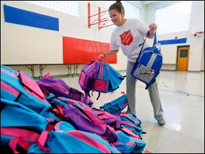 Emily Laurel, with the Salvation Army, picks-up backpacks form a huge pile to hand out.