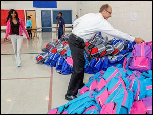 Jason Bartschy, right, on the The Salvation Army Board of Directors, gets backpacks to hand out.