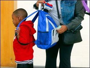 Laticia Holmes, right, helps put new socks and school supplies in the backpack of her son Malachi Winston, 4, as they head out of The Salvation Army.