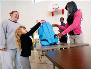 Sheyenne Davis, 5, from Toledo, marvels at her new backpack while her mother Brandy Baker, left, stands nearby. Volunteers Jerrae McGee, right, and  Marcus Lezey, center, work the event.