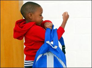Malachi Winston, 4, right, from Toledo, holds a backpack almost his size.