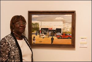 Willie N. Shahraki-Heard poses with her oil painting, '‍The Old General Store.' It's at Myles Baker Street, a cafe at 434 E. Wooster St., Bowling Green. The painting won Best of Show at this summer's Northwest Ohio Community Art Exhibition.