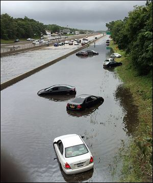 Vehicles are submerged on a flooded section of Sunrise Highway, in East Islip, N.Y., on New York's Long Island.