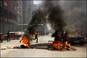 Egyptian supporters of ousted President Mohammed Morsi block a road by setting waste on fire in Matariya Square, Cairo, Egypt, today.