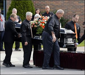The casket of race car driver Kevin Ward Jr., is taken from a hearse before being carried into South Lewis Central School before a funeral on today in Turin, N.Y.
