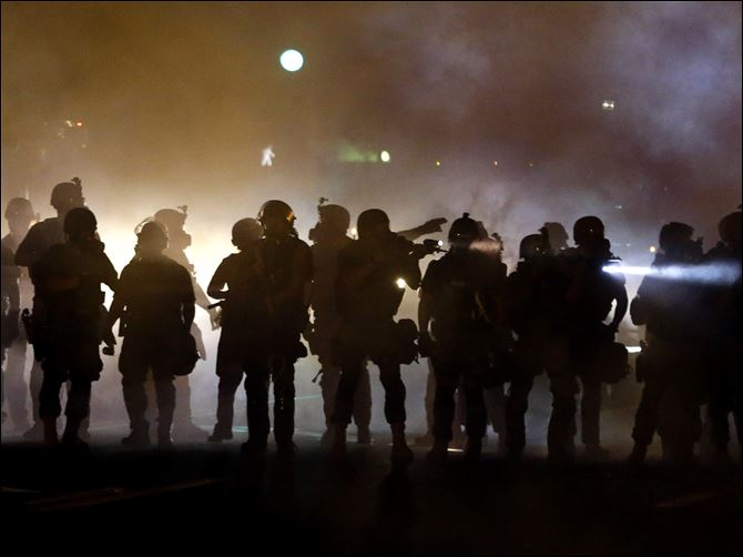 Police Shooting Missouri Police walk through a cloud of smoke as they clash with protesters Wednesday night in Ferguson, Mo.