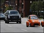 The Elio tools around in traffic in Royal Oak, Mich. The vehicle can reach tops speeds of 100 miles an hour, and it gets an estimated 84 mpg on the highway and 49 mpg in the city.