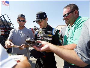 Kasey Kahne signs autographs for fans.