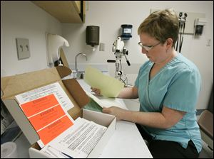 A nurse goes over paperwork from a rape kit in the emergency room at Mercy St. Vincent Medical Center.