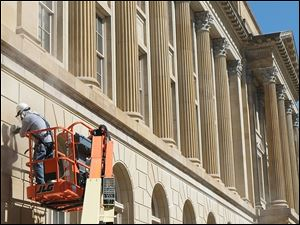 William Burgos of The Tradesmen Group Inc. of Plain City, Ohio, grinds joints on the James M. Ashley and Thomas W. L. Ashley federal courthouse on Spielbusch Avenue in Toledo.
