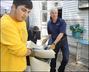 Michigan Gov. Rick Snyder, right, and  volunteer  Ali Emamdjomeh, remove damaged carpet Friday from the basement of the home of Matthew and Kathy Cahaney in Royal Oak, Mich.