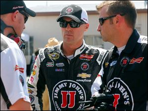 Kevin Harvick, center, talks to his crew at Michigan International Speedway.