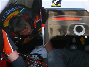 A Tony Stewart Foundation sticker is on his car while the crew works on his car for Jeff Burton to drive.