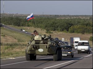 A Russian military vehicle maneuvers on a road behind an aid convoy of trucks, 9 miles from the Ukrainian border in the Rostov-on-Don region, Russia, Friday.
