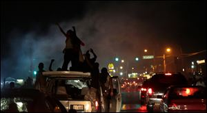 Smoke from a tire burnout rises over protestors on West Florissant Avenue in Ferguson on Friday.