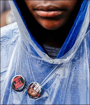 A man wears buttons of support as he visits the site where Michael Brown was shot and killed.