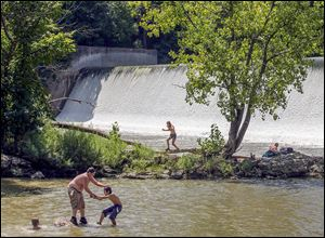People play in the water near the Ballville Dam on the Sandusky River. Some worry that the plan to dismantle the dam will allow all of the trapped sediment to flow into Lake Erie, possibly worsening algal blooms.