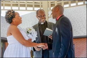 The Rev. Robert Davis, the father of the groom, conducts the marriage ceremony Saturday between Miriam Reeves and Mark Davis.