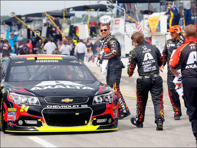 Jeff Gordon's team runs toward him while he makes his way to the winner's circle after taking the 45th Annual Pure Michigan 400 at Michigan International Speedway on August 17, 2014.
