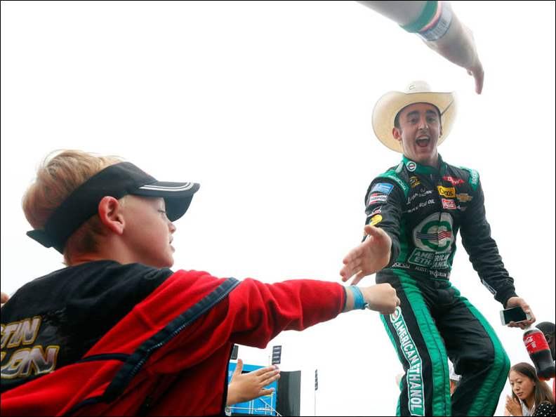 Daulton Reynolds, 7, from Saginaw, MI  reaches out to Austin Dillon during driver introductions at The Pure Michigan 400