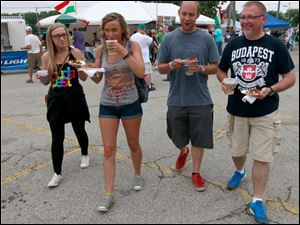 From left, The Huszti family from Grosse Pointe, Mich. (Carly, Brianna, Johny, and their dad John, Sr.) walk with drinks and Hungarian food bought from the Hungarian Club of Toledo food booth.