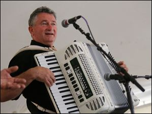 Jozsef Bakos plays the accordion with his singing partner, Janos Antal, during thefestival. The duo arrived from Szeged, Hungary, to perform in the festival.
