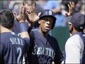 Seattle Mariners' Austin Jackson celebrates in the dugout after scoring in the sixth inning.