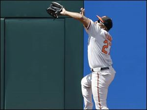 Baltimore Orioles' Delmon Young leaps to catch a ball hit by Cleveland Indians' Lonnie Chisenhall.