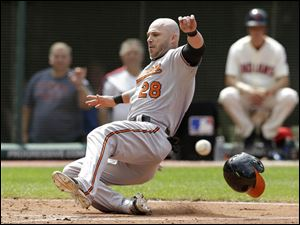 Baltimore Orioles' Steve Pearce scores ahead of the ball on a single by J.J. Hardy.