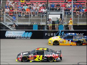 Jeff Gordon, left, takes the lead over David Ragan, right,  during  the 45th Annual Pure Michigan 400 at Michigan International Speedway on August 17, 2014.