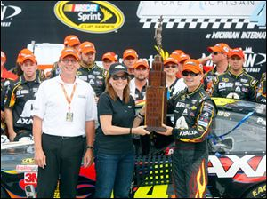 Roger Curtis, president of Michigan International Speedway, left, stands by while Mary Barra, Chief Executive Officer of General Motors, center, and Jeff Gordon, right, the winner of the 45th Annual Pure Michigan 400, hold up the trophy.