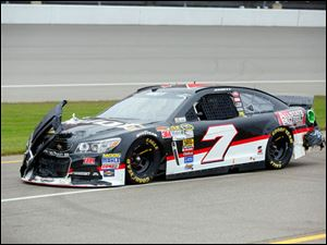 Michael Annett drives into the pits while the front of the car is askew.