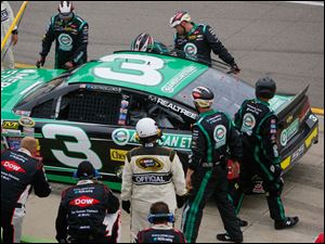 Austuin Dillon in the pit while his crew takes care of his car.